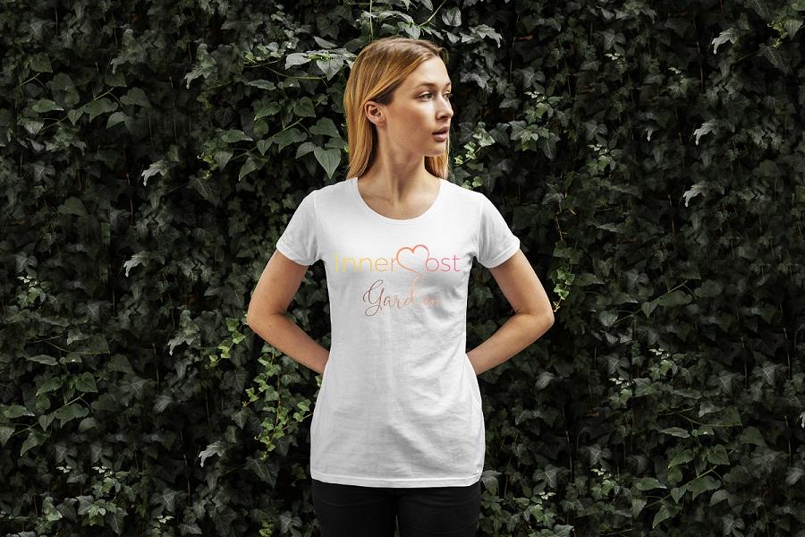 Jeune femme blonde en tee-shirt blanc sur lequel il est imprimé le logo Innermost Garden.
